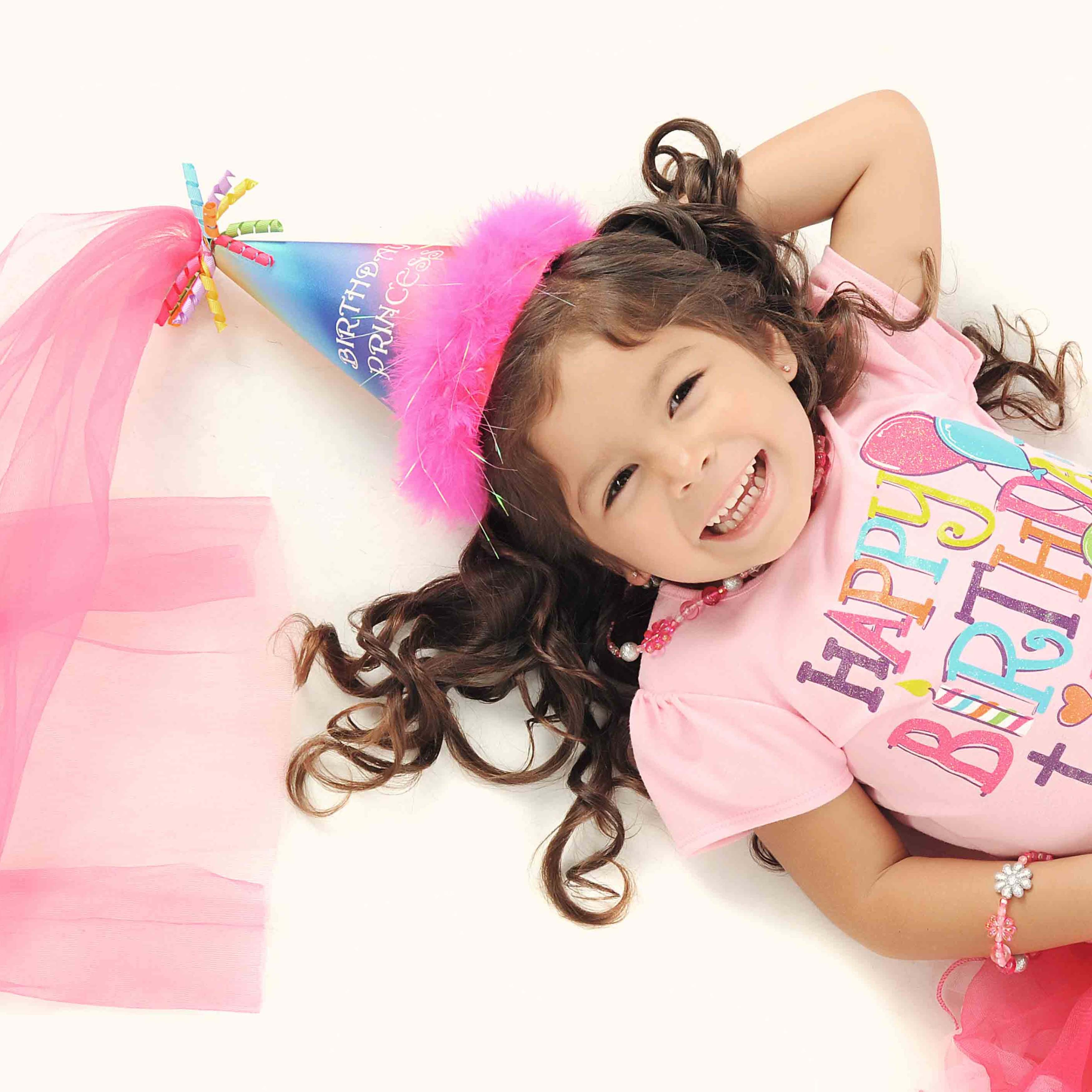 Niña tumbada sonrie el día de su cumpleaños